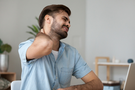 Upset man in pain touching stiff neck suffering from fibromyalgia massaging tensed muscles to relieve back joint shoulder ache tired after long sedentary computer work in incorrect posture concept. Stock Photo