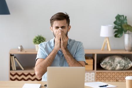 Malade au travail, un jeune homme a eu une allergie à la grippe en éternuant en soufflant en s'essuyant le nez qui coule dans les tissus, un homme allergique a attrapé froid au travail assis au bureau à domicile ayant une maladie respiratoire, concept de congé de maladie