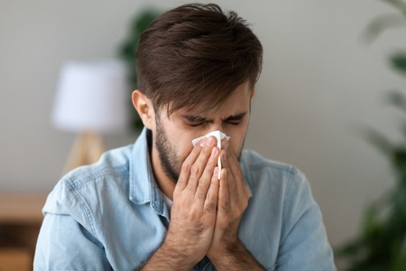 Sick man got flu grippe or allergy sneezing in handkerchief blowing wiping running nose, ill allergic guy caught cold coughing in tissue, having seasonal allergy symptoms, hay fever treatment concept Stock Photo