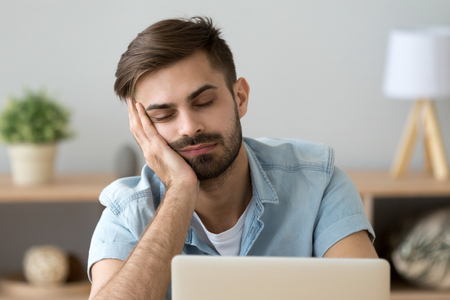Bored sleepy man feels tired drowsy resting on hand near laptop, unmotivated lazy sluggish office worker disinterested in dull work boring monotony routine wasting time, boredom lack of sleep concept
