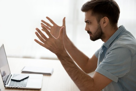 Angry annoyed young man mad about computer online problem, bad news or pc error, furious male user frustrated with discharged stuck laptop, data loss, virus attack outraged by not working device