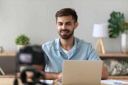 Joven orador confiado hablando en cámara digital grabando vlog sentado en el escritorio con computadora portátil, vlogger masculino o entrenador de negocios hablando blog de filmación filmación de reportajes video publicitario, coaching Foto de archivo
