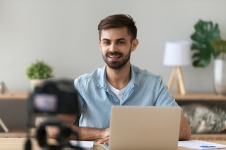 Young confident man speaker talking on digital camera recording vlog sitting at desk with laptop, male vlogger or business trainer speaking shooting blog filming reportage advertising video, coaching