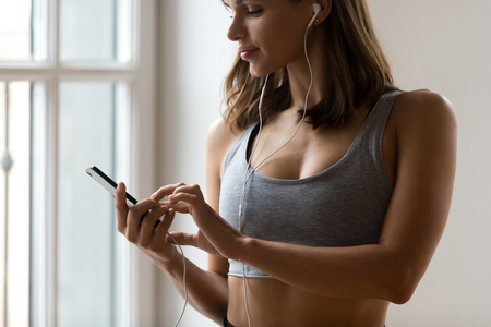 Crop close up of toned sporty female wear sportswear holding smartphone listen to music in earphones ready for training, fit woman in headphones choose track for fitness from cellphone playlist Stock Photo