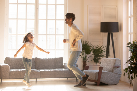 Funny happy dad and little kid daughter jumping dancing in modern light living room, cheerful cute girl having fun with father laughing moving to music, active daddy child playing together at home