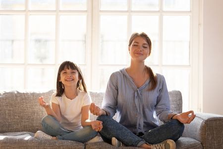 Healthy mother teaching happy kid child daughter laughing having fun doing exercises for balance harmony meditating relaxing sitting on sofa in lotus position, fit family yoga in living room at home