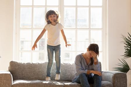 Müde, gestresste alleinerziehende Mutter mit Kopfschmerzen, die sich über lautes, aktives Kind ärgert, das auf dem Sofa springt, traurige, deprimierte, erschöpfte Mutter, die von der schwierigen ungehorsamen Kindertochter müde ist, die zu Hause spielt