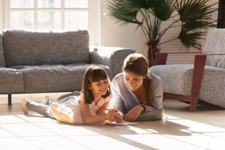 Mamá feliz ayudando a la hija del niño a dibujar con lápices de colores en un piso cálido juntos, sonriendo a la madre de la niñera enseñando a un niño lindo aprender actividad creativa jugar reír en casa en la sala de estar