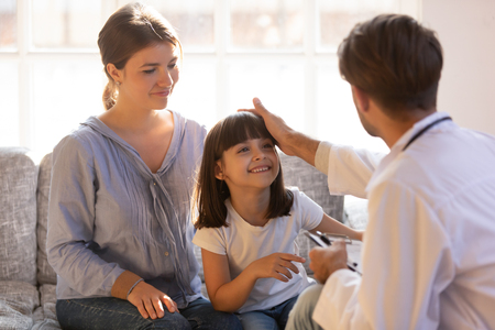 Caring male doctor stroking head of little girl patient sit on couch with mom, happy trusting child visiting talk to pediatrician showing good attitude relationships with kid at medical consultation