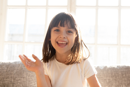 Happy cute little vlogger waving hand saying hello hi looking at camera talking to webcam, smiling kid child girl making online video call recording vlog sitting on sofa at home, portrait Фото со стока