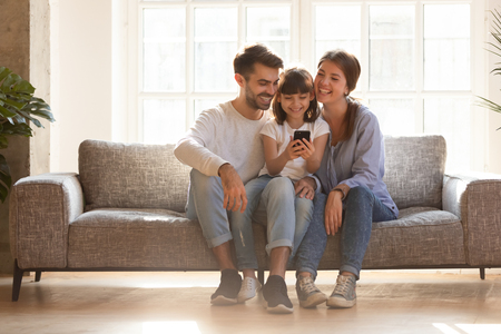 Happy family and kid daughter having fun with smartphone gadget at home, little child girl looking at phone play game using app with mom dad watching funny mobile video, making online call on couch