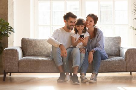 Hija de niño y familia feliz divirtiéndose con un dispositivo de teléfono inteligente en casa, niña pequeña mirando el juego de teléfono usando la aplicación con mamá papá viendo videos móviles divertidos, haciendo llamadas en línea en el sofá Foto de archivo