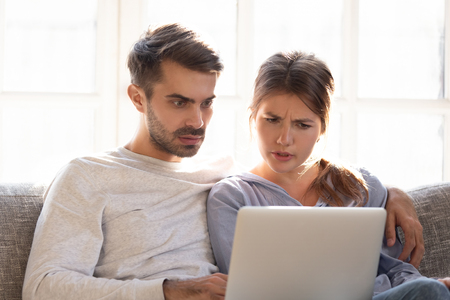 Confused baffled wife and shocked frustrated husband reading online news looking at stuck laptop, bewildered young couple in disbelief perplexed by computer problem email or system failure message Stock Photo