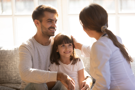 Caring friendly doctor stroking head of cute girl patient sitting on dads lap, father with child visiting pediatrist showing good attitude to child trusting pediatrician, children medical health care