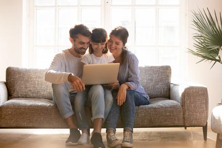 Familia feliz, papá, mamá con hija niño usando una computadora portátil juntos en el sofá, padres sonrientes y niña pequeña ven videos divertidos, hacen compras por Internet, hacen llamadas en línea en un día soleado en la sala de estar Foto de archivo