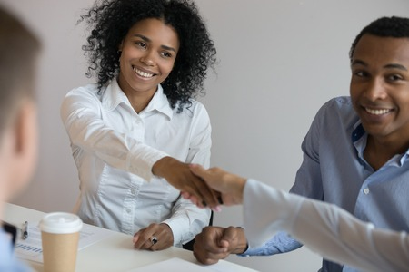 Attractive biracial millennial businesswoman starting negotiations with business partner shaking hands, show respect and nice to meet you meaning common phrase used when meeting a new person concept Stock Photo