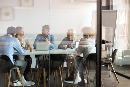 Dział reklamy burza mózgów w sali konferencyjnej nowoczesnego biura za zamkniętymi drzwiami, widok przez szklaną ścianę. Zróżnicowany personel prowadzony przez dyrektora generalnego omawiający nowe projekty, dzielenie się pomysłami i sposobami sprzedaży