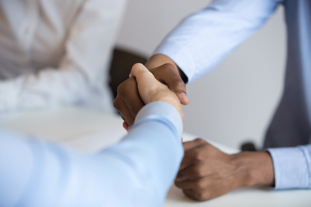 Multi-ethnic businesspeople sitting at desk during negotiations handshaking greeting each other or celebrating achieved results, close up black and caucasian business partners successful deal concept