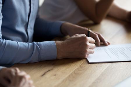 Cerca de la mano del hombre sosteniendo un bolígrafo y firmando un documento legal contrato de arrendamiento comprando una propiedad. Nuevo empleado afirmando el acuerdo en papel con la firma obteniendo un puesto en el concepto de recursos humanos de la empresa