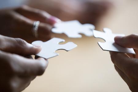 Nahaufnahme der Hände von afroamerikanischen und kaukasischen Mitarbeitern multinationaler Teamkollegen, die weiße Puzzleteile halten, Menschen suchen und Lösungen finden. Teambuilding, Teamwork und Supportkonzept