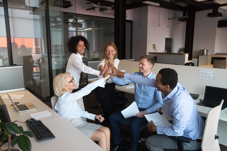 Cheerful coworkers different ages and ethnicity gathered together in coworking shared office room giving high five celebrating congratulating each other with good deal and success at common business. Stock Photo