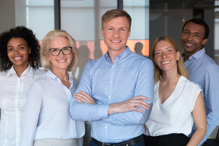 Smiling chief or professional business coach looking at camera posing in office together with multi-ethnic happy team, successful startup founder company owner and employees members portrait concept