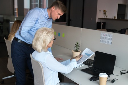 Serious company ceo mature businesswoman sitting at desk talking with employee male worker pointing on mistakes in financial report or sales statistics, having questions claims to agreement conditions Stock Photo