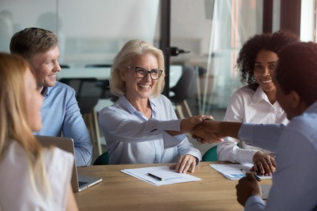 Middle aged woman executive manager company representative welcoming business partner while sitting in modern office boardroom or trainer shake hands with participant before starting education meeting