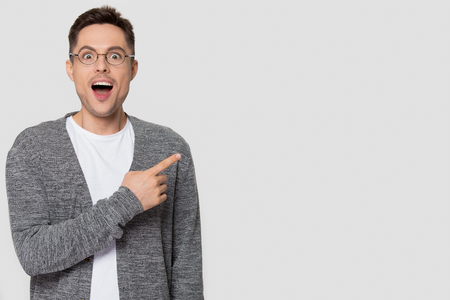 Amazed funny man in glasses pointing finger aside at copy space excited by unbelievable offer looking at camera, surprised male customer advertise product service isolated on studio blank background
