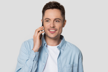 Happy young man holding cellphone talking on mobile phone, smiling guy caller making call enjoy conversation speaking by smartphone isolated on white grey blank studio background, telecommunications Stock Photo