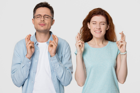 Superstitious young couple crossing fingers wish for good luck concept, funny stressed man and woman begging for help hoping for win believe in superstition isolated on grey white studio background