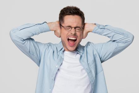 Hombre joven enojado obstinado que cubre sus oídos escuchando ruidos fuertes molestos, chico estresado loco gritando sintiendo dolor de oído sufre de migraña o dolor de cabeza aislado sobre fondo blanco gris de estudio en blanco