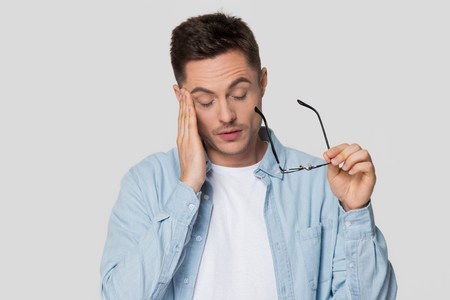 Upset young man feeling eyestrain taking off glasses, tired guy holding eyeglasses suffer from headache massaging temple isolated on white grey studio background, eye fatigue strain migraine concept