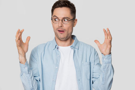 Funny shocked young man nerd looking at hands showing something huge, amazed confused guy in glasses bragging with large big size exaggerating gesture isolated on white grey blank studio background