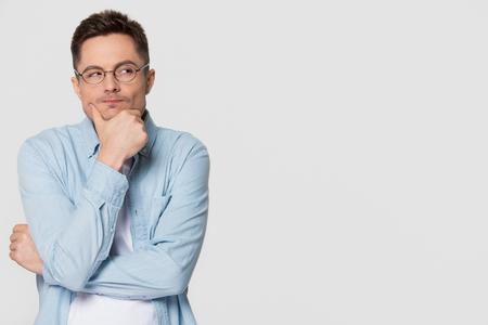 Jeune homme méfiant réfléchi regardant de côté l'espace de copie se sentant sceptique, douteux, méfiant et rusé pensant tenant la main sur le menton isolé sur fond de studio blanc gris