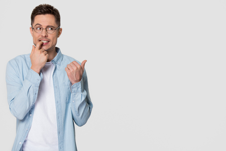 Nervous or doubtful young man looking aside wondering pointing finger at copy space, stressed worried guy biting nail feeling confused embarrassed hesitating isolated on white grey studio background