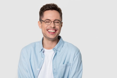 Happy man wearing glasses laughing at funny hilarious silly joke, young guy with cheerful face smiling chuckling giggling isolated on white grey studio blank background, laughter and humor concept