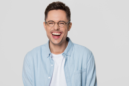 Funny guy nerd wearing glasses laughing at humorous hilarious silly joke looking at camera isolated on white grey blank background, happy cheerful young man chuckling giggling having fun portrait Stock Photo