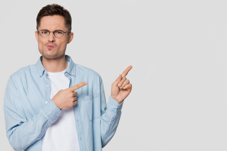 Confused bewildered young man pointing fingers at copy space aside feeling doubtful distrustful, perplexed dubious guy in disbelief looking at camera isolated on grey white blank studio background