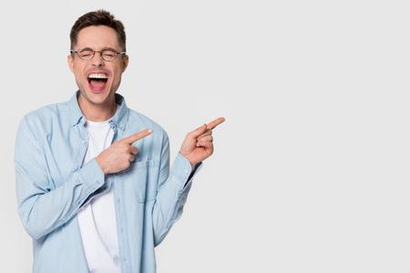 Hombre joven divertido feliz riendo o sintiéndose emocionado que señala el dedo a un lado en el espacio de la copia, alegre chico lleno de alegría gritando de alegría estalló con publicidad de risa aislado sobre fondo blanco de estudio Foto de archivo