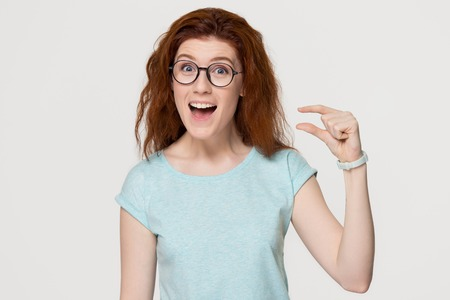 Funny excited redhead woman showing something very tiny little size by fingers, happy red-haired girl with open mouth amazed by small prices looking at camera isolated on white grey studio background Stock Photo