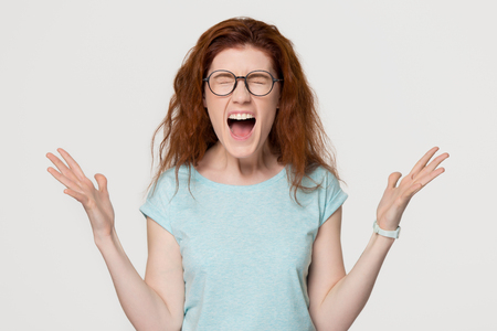 Angry mad outraged stressed young redhead hysterical girl yelling shouting loud, overjoyed excited red-haired woman with emotional face screaming with joy isolated on white grey studio background