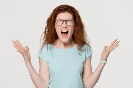 Wściekły szalony oburzony zestresowany młody rudowłosy histeryczny dziewczyna krzyczy głośno krzycząc, zachwycony podekscytowaną rudowłosą kobietą z emocjonalną twarzą krzyczącą z radości na białym tle szarym studio
