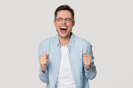 Empollón del joven divertido emocionado lleno de alegría que grita de alegría celebrando la victoria aislada en el fondo gris blanco del estudio, ganador del tipo afortunado feliz en los vidrios motivado por el logro de la meta de la victoria del éxito Foto de archivo