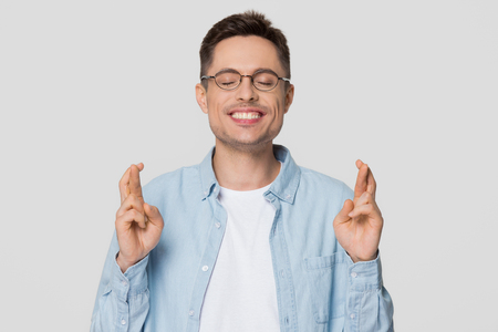 Funny superstitious young man hoping wishing for good luck crossing fingers, hopeful guy student anticipating dream come true isolated on grey white studio background, superstition beliefs concept