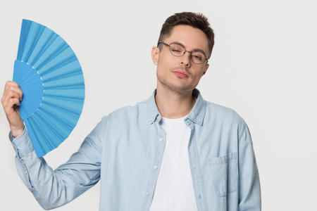 Overheated young man sweating feeling uncomfortable suffering from heat stroke problem isolated on white grey studio background, funny sweaty guy waving fan cooling in hot summer weather swelter