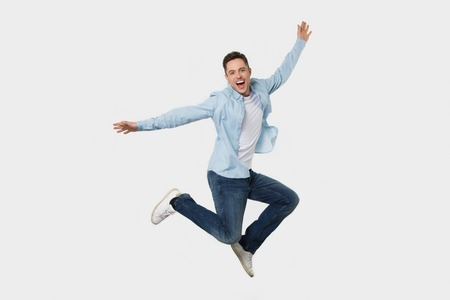 Happy cheerful young man jumping feeling joy, excited funny energetic guy winner fly rejoicing success looking at camera screaming isolated on white grey studio background, full body length portrait 版權商用圖片