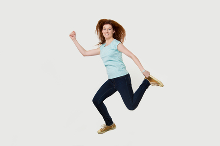 Happy active fit young woman running hurrying to gym jumping in air looking at camera isolated on white grey studio background, smiling female runner in dynamic motion full body length portrait