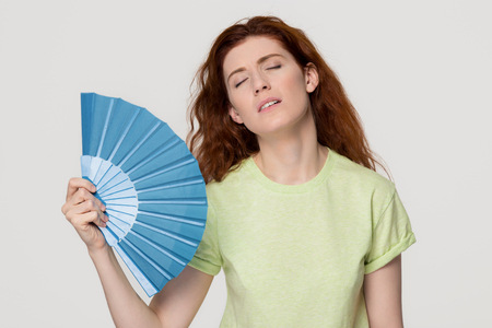 Overheated redhead woman sweating feel uncomfortable suffer from heat stroke perspiration problem, tired sweaty lady waving fan cooling in hot summer weather isolated on white grey studio background Stock Photo