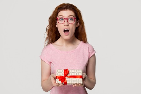 Amazed red-haired young woman in glasses holding gift box looking at camera, shocked excited red-headed girl feel surprised advertising present package isolated on white grey studio blank background